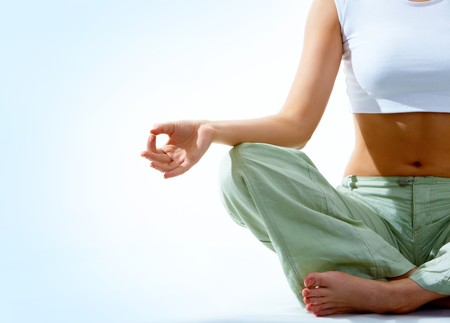 meditation isolated white: Close-up of female's torso during meditation with legs crossed and hand being kept on her right knee Stock Photo