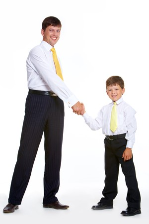 Portrait of father and son standing and handshaking while looking at camera on white background photo