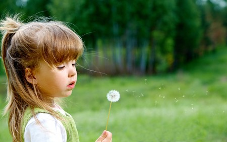 Profile of cute girl with white dandelion looking at it in the park photo