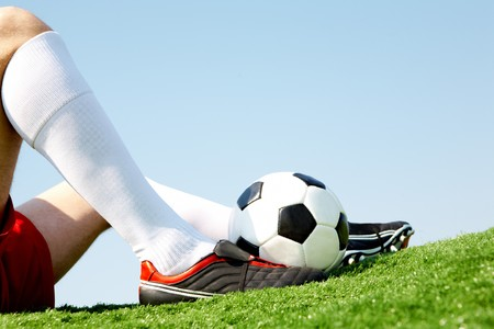 football boots: Horizontal image of seated player leg with soccer ball near by