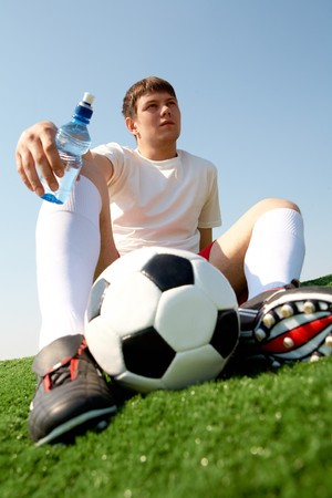 grassfield: Photo of pensive soccer player seated on green grass-field against blue sky