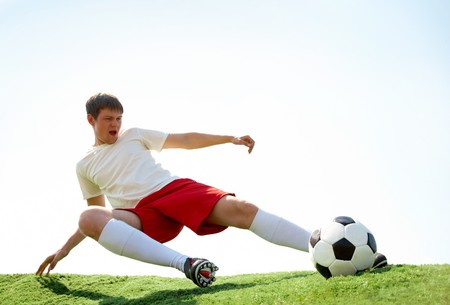 grassfield: Portrait of soccer player kicking ball during game