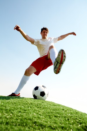 kicking ball: Portrait of soccer player before kicking ball on football field