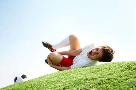 terrain foot: Image du joueur de soccer couchée et crier de douleur