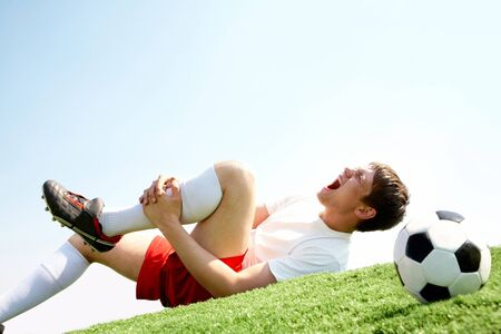 play ground: Image of soccer player lying down and shouting in pain