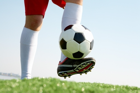 soccer boots: Horizontal image of soccer ball being kicked by footballer Stock Photo