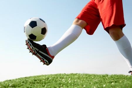 Horizontale beeld van het voet bal worden geschopt door voetballer tegen blauwe hemel