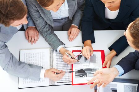 group strategy: Above view of business partners discussing new project at meeting Stock Photo