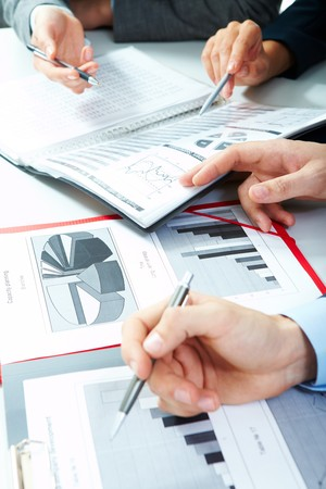 Vertical image of business partners hands over papers discussing them Stock Photo - 6981344