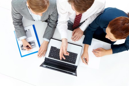 Photo of confident man pointing at laptop and explaining new project to smart females photo