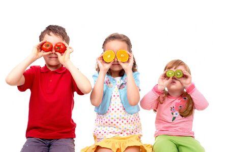 ni�os contentos: Retrato de tres amigos, celebraci�n de verduras y frutas antes de ojos Foto de archivo
