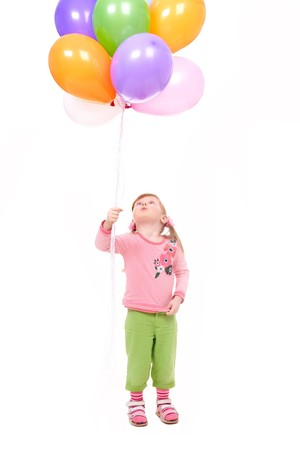 amused: Image of small girl with helium balloons looking upwards at them