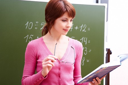 Portrait of young teacher reading book by blackboard in the classroom photo