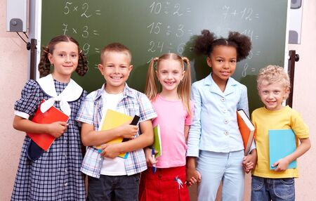 Image of curious schoolchildren standing by blackboard and looking at camera in the classroom Stock Photo - 7020596