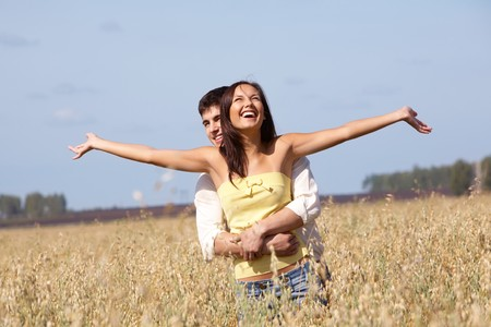 Image of joyful girl stretching arms while being embraced by her boyfriend  photo