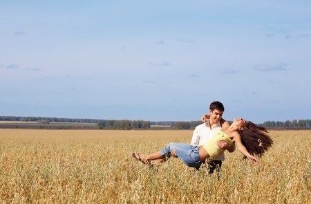 Image of handsome man holding beautiful girl while she laughing  photo