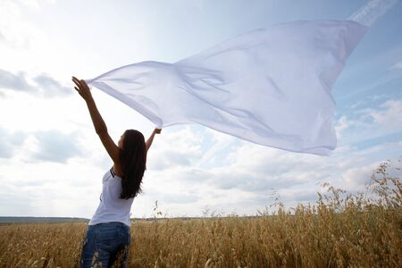 Back view of charming girl raising her arms with chiffon shawl in wheat field photo