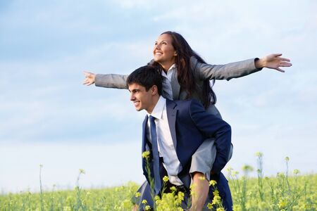 life partners: Portrait of happy business partners enjoying life and freedom in meadow