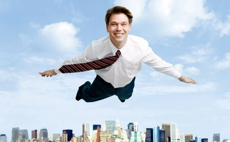 flying man: Conceptual image of smiling businessman flying in the clouds Stock Photo