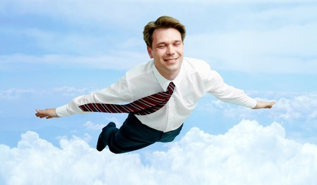 man flying: Conceptual image of smiling businessman enjoying flying in the clouds