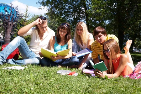 several: Portrait of smart friends reading books in park together