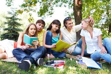 Portrait of teens talking and reading books in park at summer photo