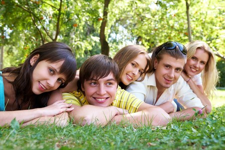 Photo of several happy friends lying in row and relaxing outdoors photo