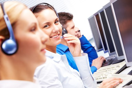 customer assistant: Smart operator sitting between co-workers during telephone conversation