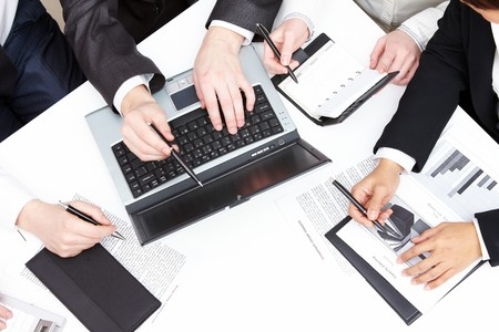 consulting team: Photo of male hand pointing at laptop during group discussion