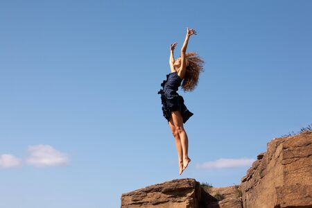 dynamic: delighted female leaping over rocky cliff in excitement