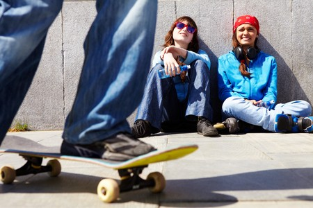 Two teen girls sitting on asphalt and watching their friend skateboarding outdoors photo