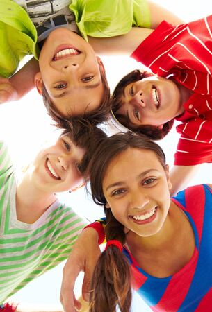 group of teenagers: Below view of several happy friends standing head by head to each other