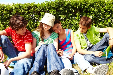 Portrait of friendly teens sitting on green grass and interacting photo