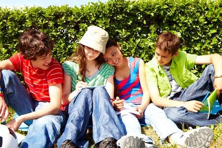 adolescentes estudiando: Retrato de adolescentes amistosos sentado sobre c�sped verde e interactuar  Foto de archivo
