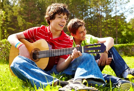 lad: Portrait of happy lad playing the guitar with his friend near by