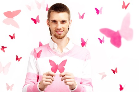 Image of smart guy with pink paper butterfly in hands looking at camera and smiling photo