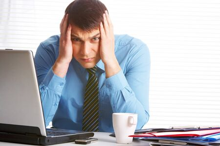 Portrait of stressed businessman touching his head and looking at camera Stock Photo - 7059892