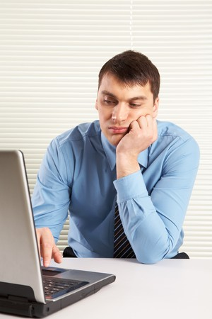 Portrait of bored businessman looking at laptop monitor while typing photo
