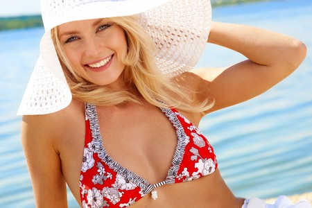 blonde girls: Image of luxurious woman in bikini and hat relaxing on the seashore