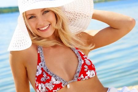 chicas guapas: Imagen de mujer lujosa en bikini y sombrero relajante sobre la orilla del mar
