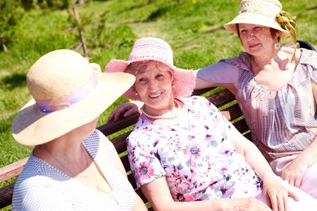 Portrait of three senior females sitting on bench at summer and chatting Stock Photo - 7059929