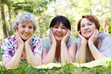Portrait of three aged women resting on grass and looking at camera with smiles Stock Photo - 7059926