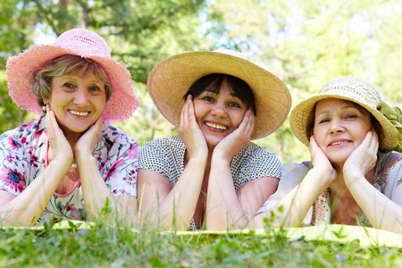 headcloth: Portrait of three aged women in elegant hats resting on grass