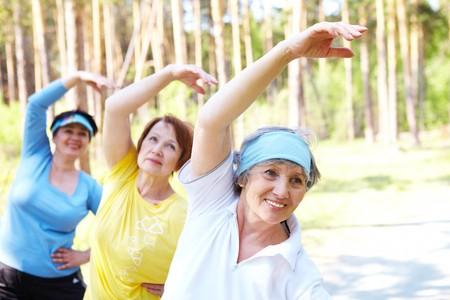 gimnasia: Retrato de la mujer de edad con sus brazos alzados mientras hace ejercicio f�sico