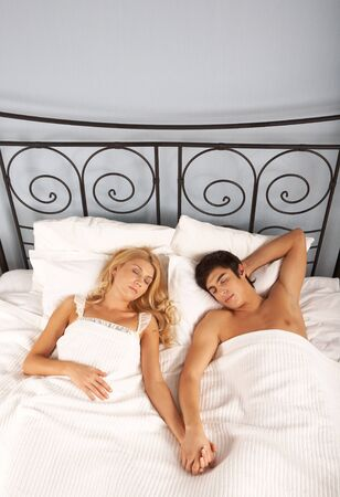 pillow sleep: Photo of serene woman and man holding by hands while sleeping