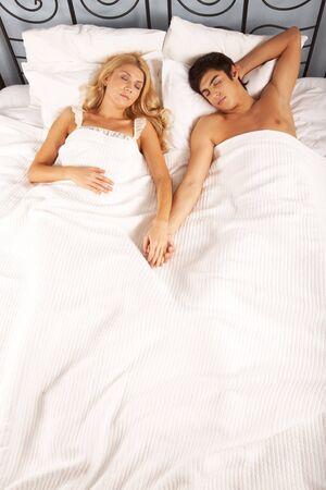 pareja en la cama: Foto de Serena de la mujer y el hombre que sostiene con las manos mientras se duerme