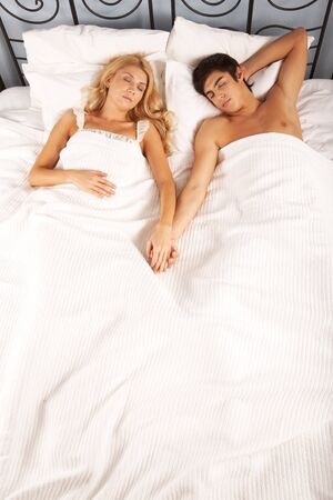 bedroom bed: Photo of serene woman and man holding by hands while sleeping