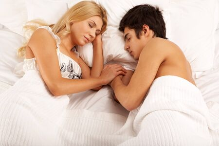 Horizontal image of young couple sleeping at night photo