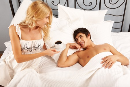 Horizontal image of young woman offering cup of coffee to her husband in the morning photo