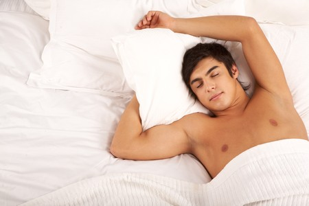 Image of man with one hand under pillow sleeping in bed photo